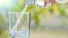 Wasser wird in ein Glas eingecshenkt