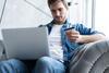 Junger Mann mit Laptop und PAYBACK Karte