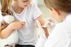Kleines Mädchen hält ein Kuscheltier während es geimpft wird