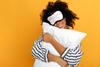 Frau mit Kissen im Arm und Schlafmaske auf dem Kopf