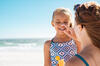 Hautkrebs-Vorsorge: Mutter trägt bei ihrer Tochter Sonnencreme im Gesicht auf