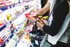 Person liest im Supermarkt die Nährwertangaben auf einem Produkt durch