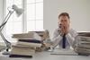 Mann sitzt an einem Schreibtisch voller Unterlagen und reibt sich die Augen