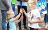 Kleines Mädchen zeigt einem kleinen Jungen stolz seine Medaille der BIG Family Games