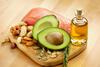 Nüsse, Avocados, Lachsfilet und ein Fläschchen mit Öl auf einem Holzbrettchen