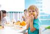 Kind hält sich ein Stück Paprika an den Mund