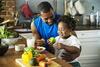 Vater und Kind sitzen an einer Küchentheke und essen Obst