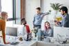 Stress: Kolleginnen und Kollegen diskutieren im Großraumbüro eine Projektidee