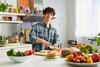 Junger Mann bereitet an einer Küchentheke Essen zu