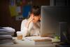 Stress: Frau sitzt am Schreibtisch und hält Hände vor ihr Gesicht