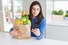 Frau mit Lebensmitteln und Smartphone