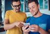 2 junge Männer mit Blick auf's Smartphone