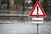 Ein Hochwasser-Warn-Schild vor einem Fahrrad im Wasser