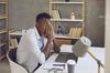 Junger Mann sitzt am Schreibtisch und reibt sich gestresst die Augen