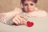 Traurige Frau berührt mit dem Zeigefinder ein kleines rotes Herz