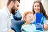 Junge schaut sich beim Zahnarzt seine Zähne in einem Handspiegel an