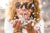 Nahaufnahme einer Frau mit blonden Locken, die buntes Konfetti aus ihren Händen pustet