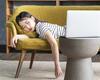 Junge Frau liegt gelangweilt auf dem Sofa und schaute einen Film auf dem Laptop