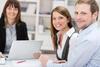 Zwei Frauen und ein Mann im Gespräch mit Laptop