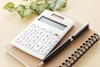 Taschenrechner, Block und Kugelschreiber auf einem Tisch