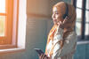 Junge Frau mit Kopftuch hört Musik über Kopfhörer