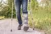 Mann mit Krücken und Schiene am Bein