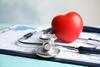 Stethoskop, rotes Herz und Kardiogramm auf einem Tisch