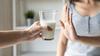 Person lehnt mit einer Handgeste ein Glas Milch ab